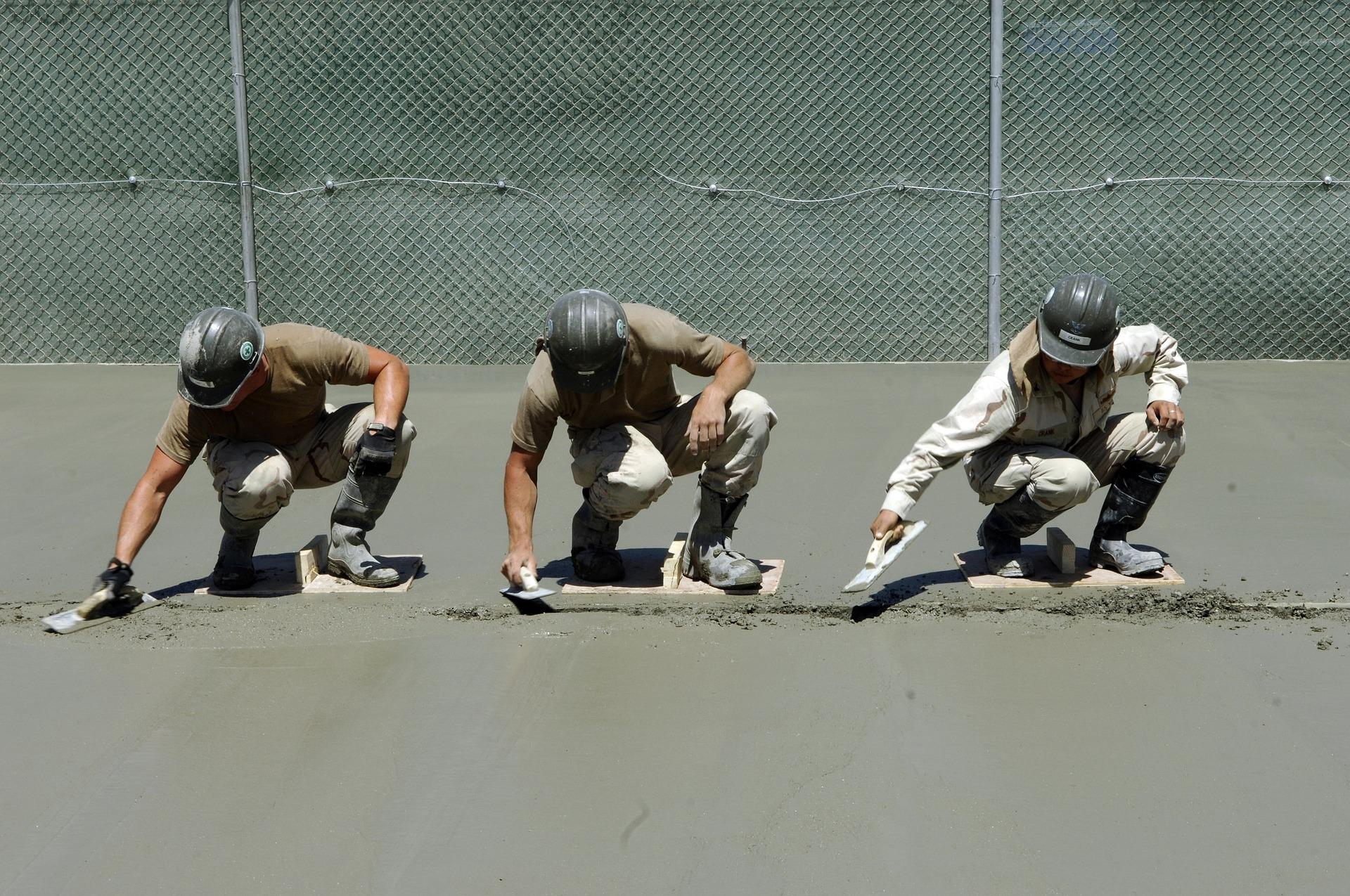 Tre arbeidere støper betongunderlag